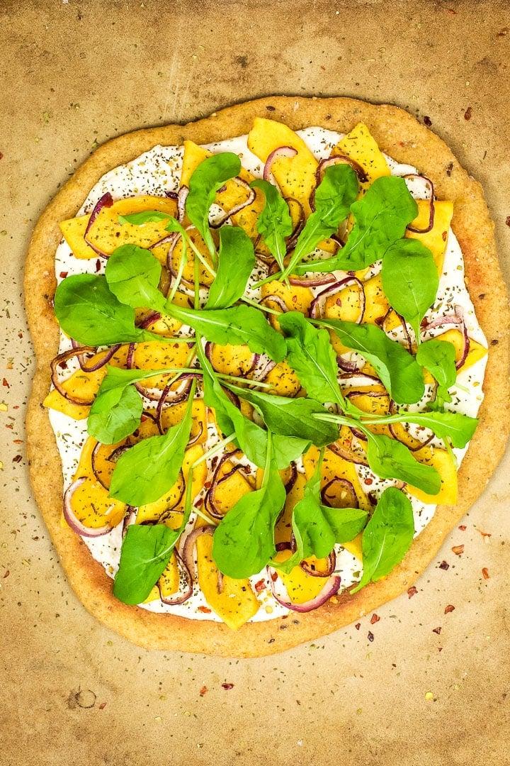 Roasted squash white pizza on pizza stone with arugula