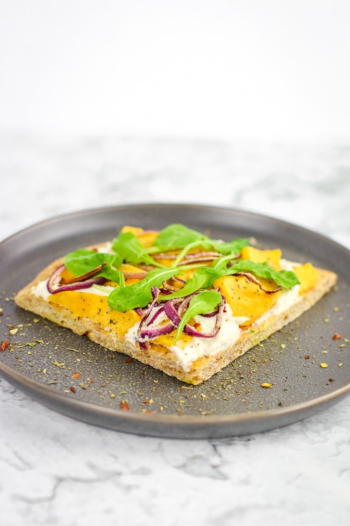 roasted squash white pizza topped with arugula on a gray plate on marble.