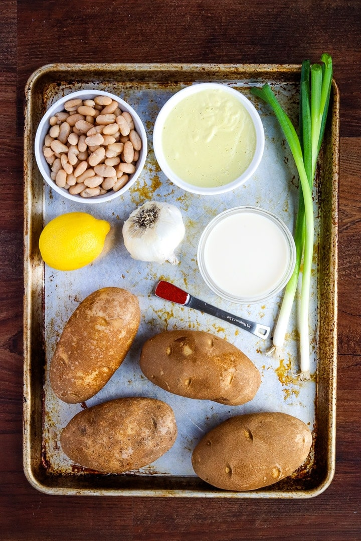 Sheet pan with ingredients: 4 baking potatoes, lemon, green onion, plant milk bowl, lemon, smoked paprika teaspoon, garlic bull, easy cheesy sauce.