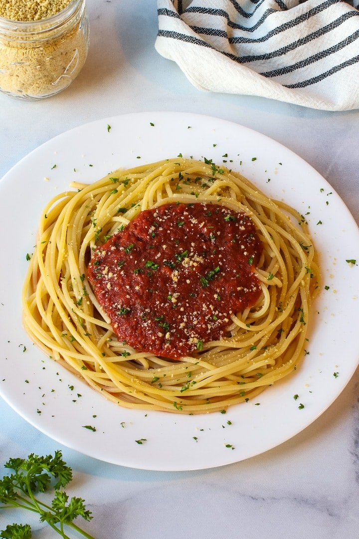 White plate of spaghetti with tomato sauce and minced parsley and parmesan on white marble.