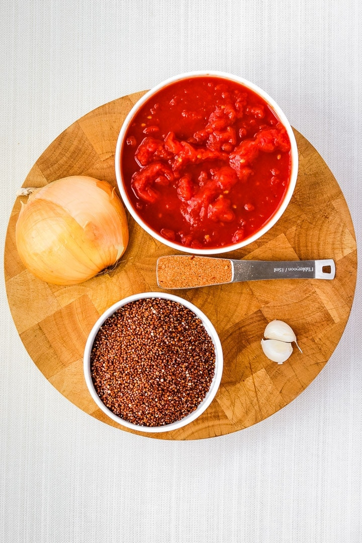 round cutting board with dish of canned tomatoes and red quinoa, with half an onion, 2 garlic cloves and a tablespoon of taco seasoning.