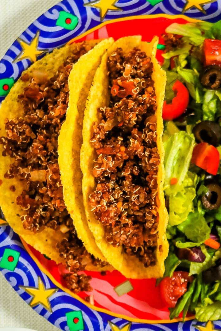 Close up of quinoa taco meat in corn tortilla shells on a festive paper plate with a die of lettuce, diced tomatoes and slices black olives.