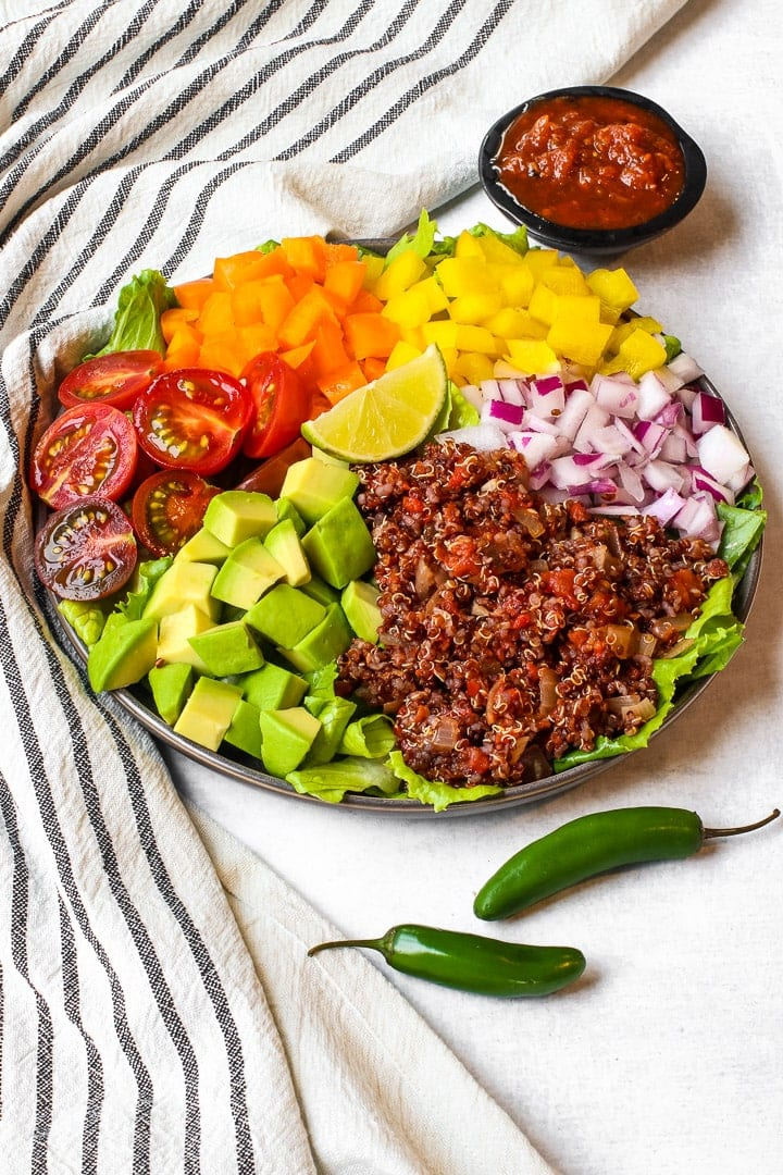 Taco salad with lettuce, halved cherry tomatoes, diced red & yellow bell pepper, diced red onion, avocados cubes and quinoa taco meat on a black striped towel with jalapeno pepper and a black dish of red salsa.