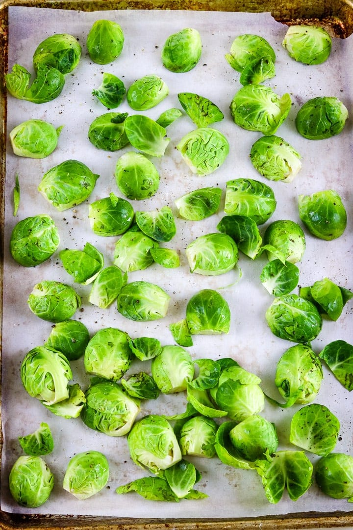 Parchment paper lined baking sheet with raw brussels sprouts halves.