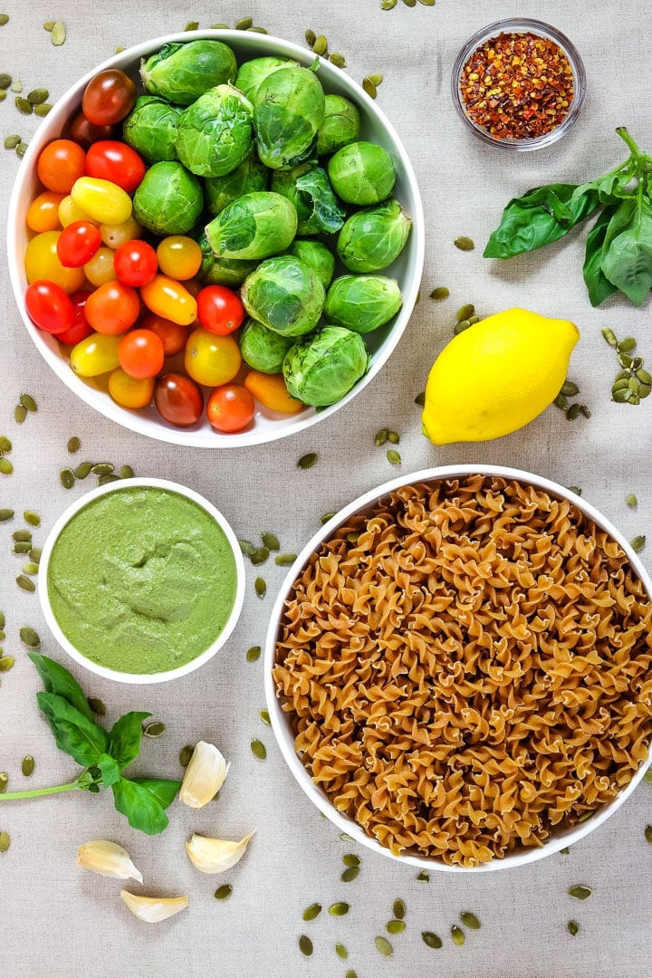 Roasted vegetable pasta Ingredients: white bowl of brussels sprouts and cherry tomatoes, white bowl of curly pasta, pesto, lemon, crushed red pepper flakes, basil and garlic on linen.