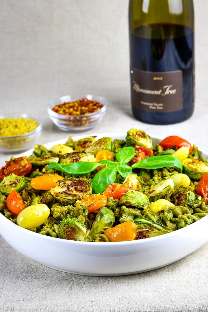 Flat white bowl of curly pasta with pesto sauce, roasted tomatoes and brussles sprouts, topped with basil sprig. Wine bottle an dishes of vegan parmesan and crushed red pepper flakes in background.