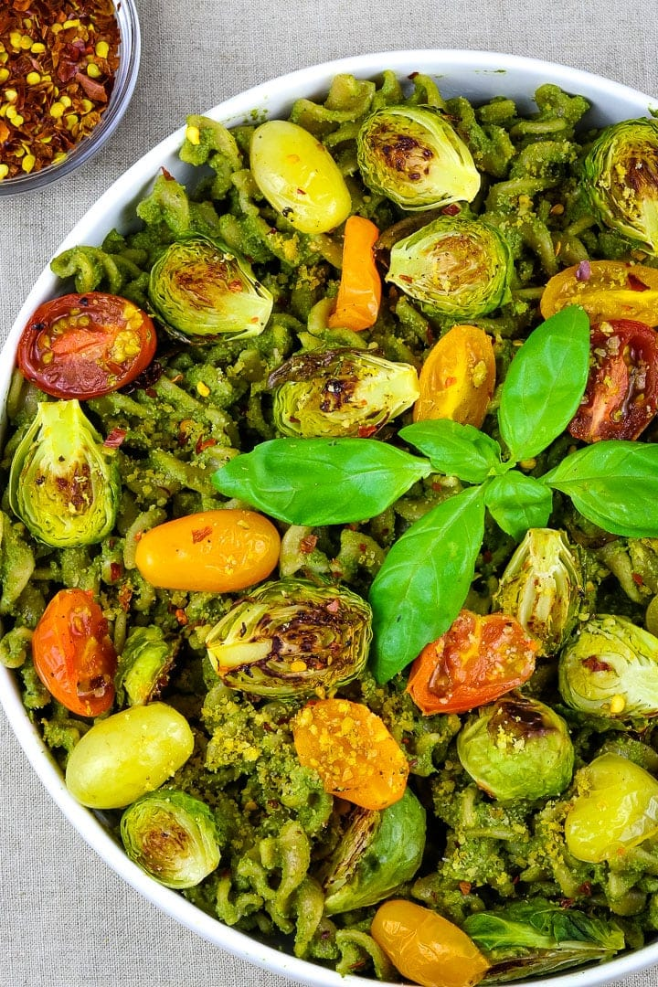 Close up of Flat white bowl of curly pasta with pesto sauce, roasted tomatoes and brussles sprouts, topped with basil sprig.