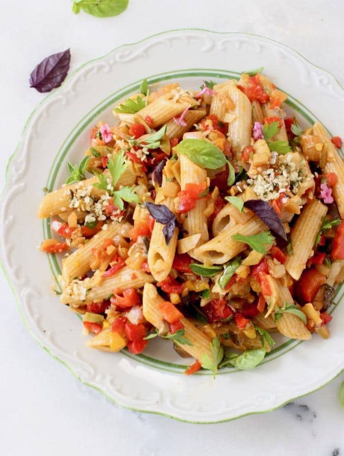 White plate with penne pasta, tomato chunks, green and purple basil leaves.