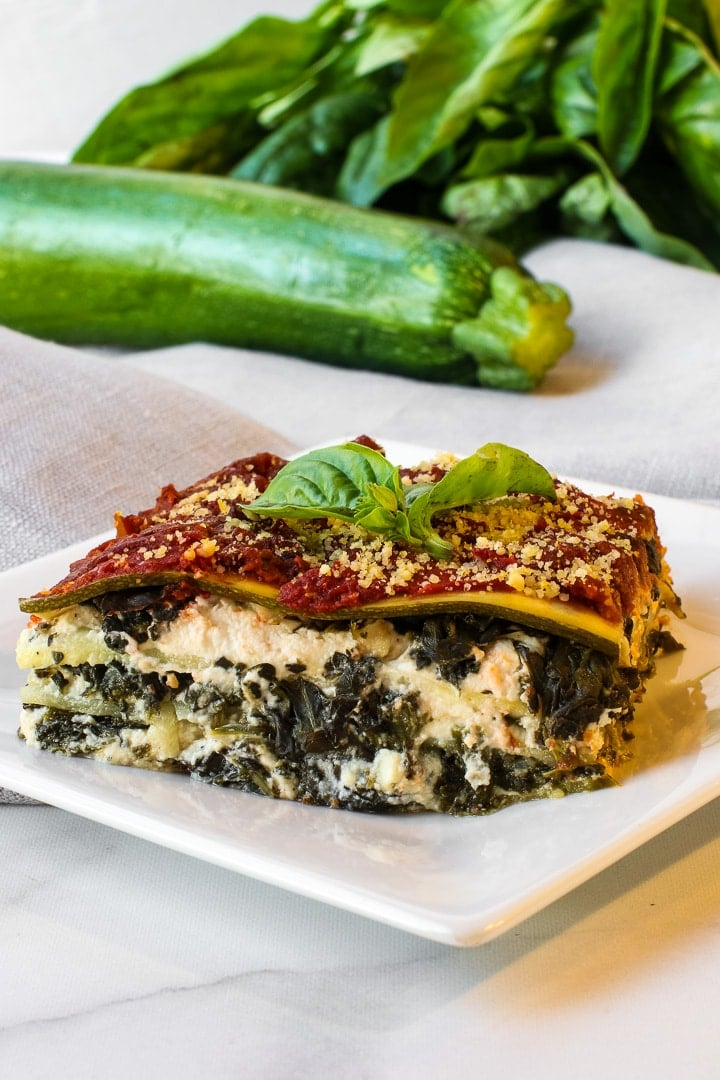 Vegan zucchini lasagna on a white plate on marble and beige napkin, with whole zucchini and basil in background.
