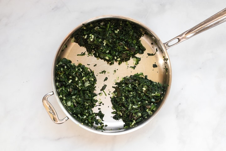 Skillet with cooked spinach, basil, garlic, and onion on marble.