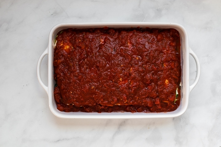 White baking dish with top layer of zucchini slices and tomato sauce spread over the lasagna on gray marble.