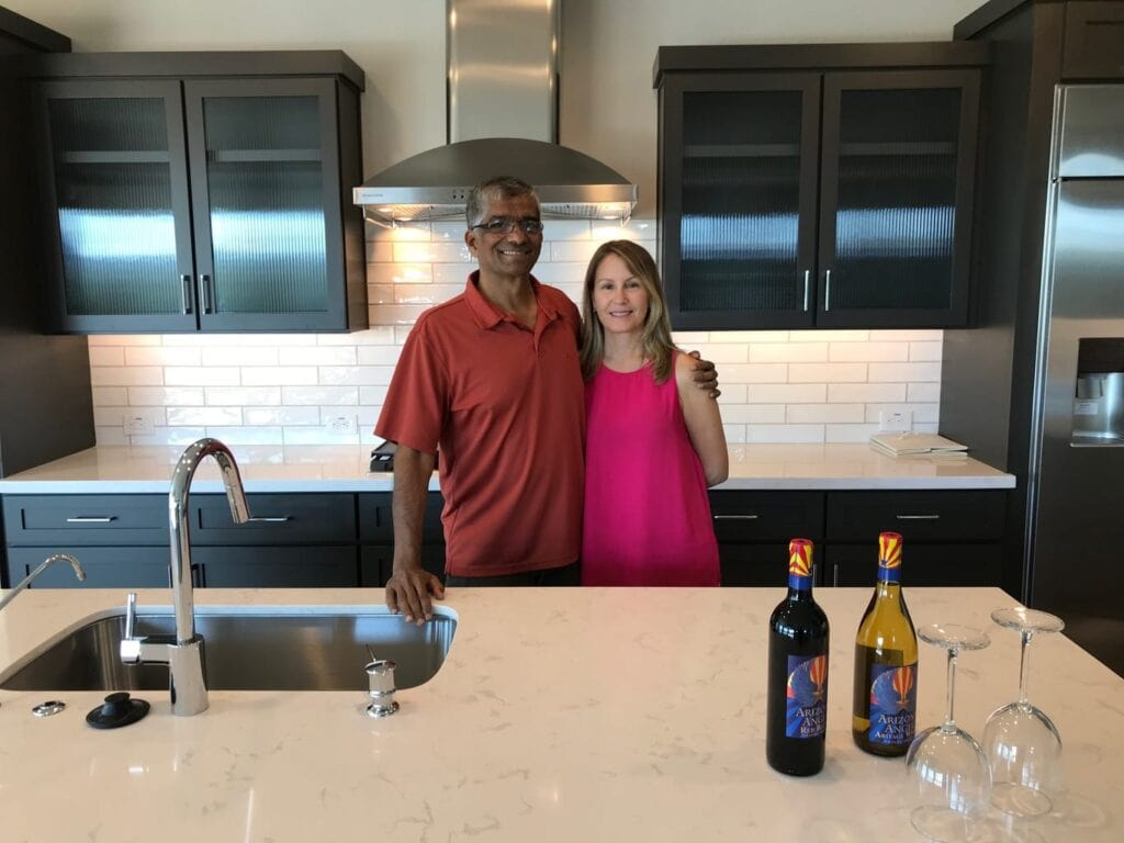 Hemant and I standing behind the island in our new kitchen in Arizona. Brown cabinets, white marble counters, white subway tile backsplash, stainless steel range hood.