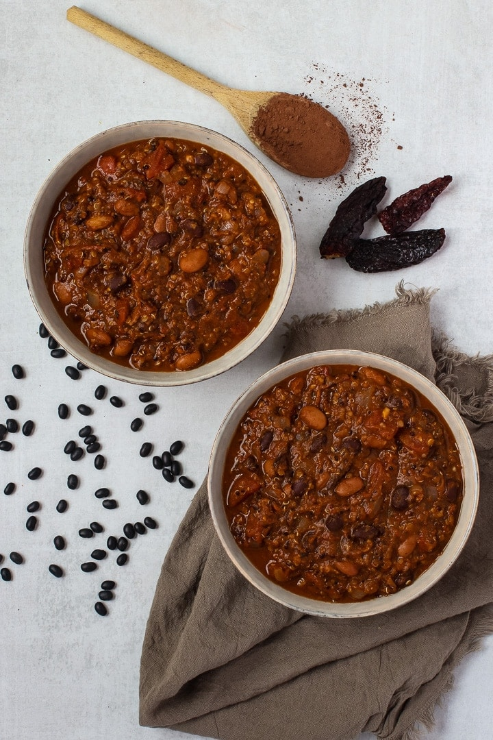 2 bowls of vegan pumpkin chili mole with on a brown towel, with dried black beans, a wooden spoon with cocoa powder and dried chilis.l