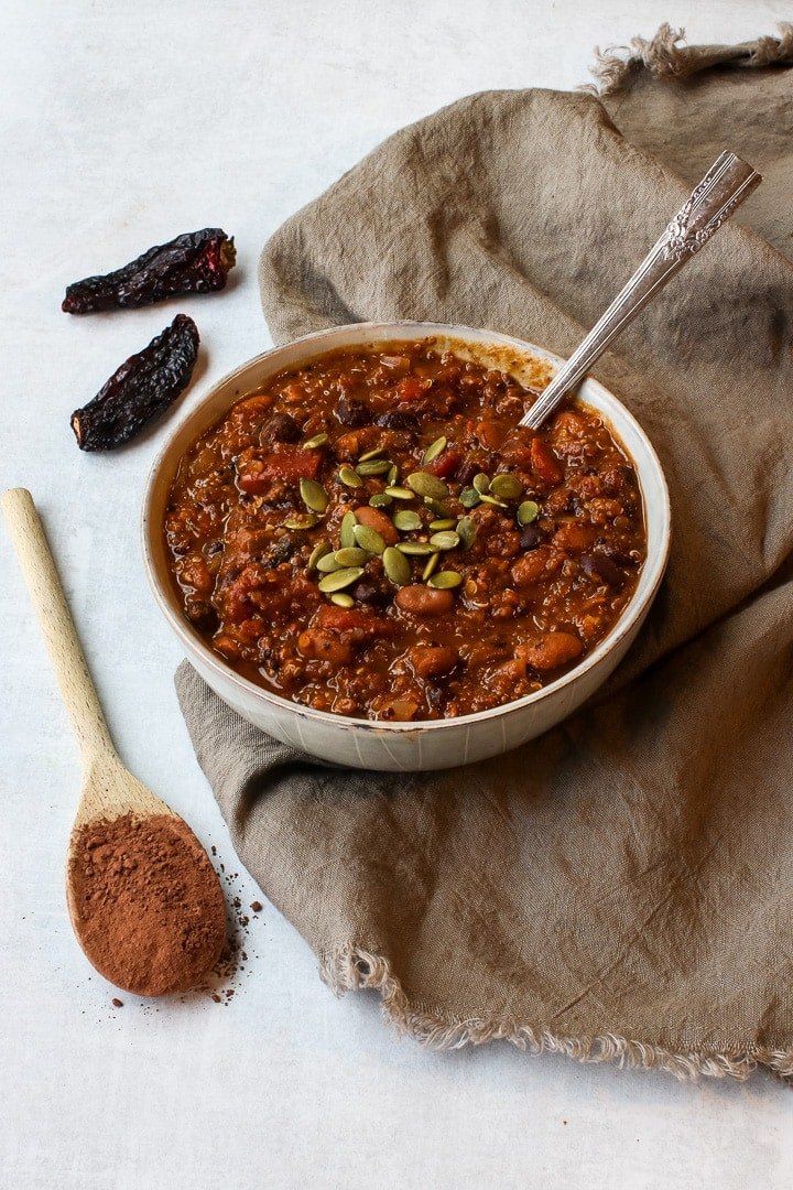 Bowl of pumpkin chili mole with pepita seeds and a spoon on a brown towel, with wooden spoon with cocoa powder and dried chilis.l
