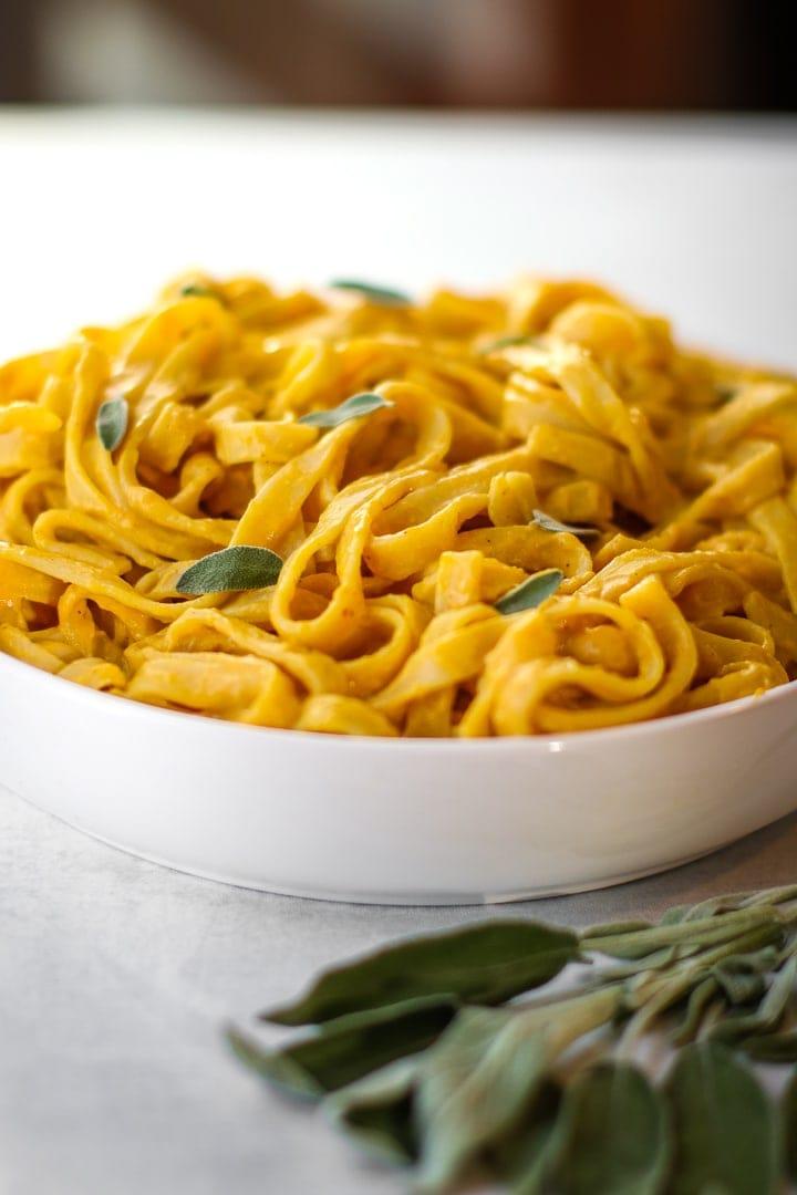 Fettucine with vegan pumpkin pasta sauce & fresh sage in a white bowl.