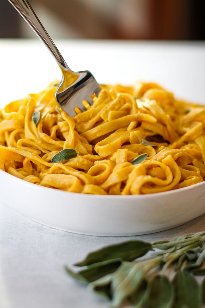 white bowl of fettuccine with pumpkin pasta sauce with fresh sage and a fork