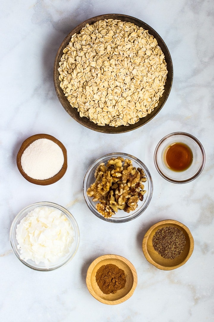 Bowls of rolled oats, nuts, flax, vanilla, coconut flakes, erythritol on white marble.