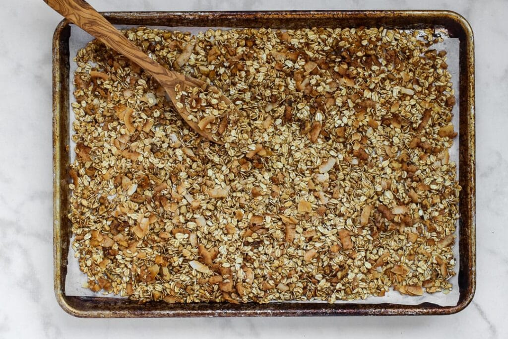 Granola spread out on a parchment paper lined baking sheet with wooden spoon.