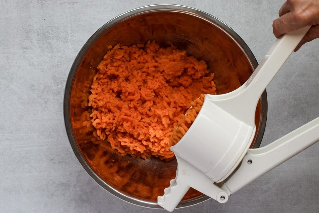 Ricing sweet potatoes into a stainless steel bowl.
