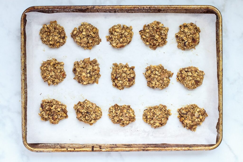 oatmeal cookies on a parchment paper lined baking sheet.