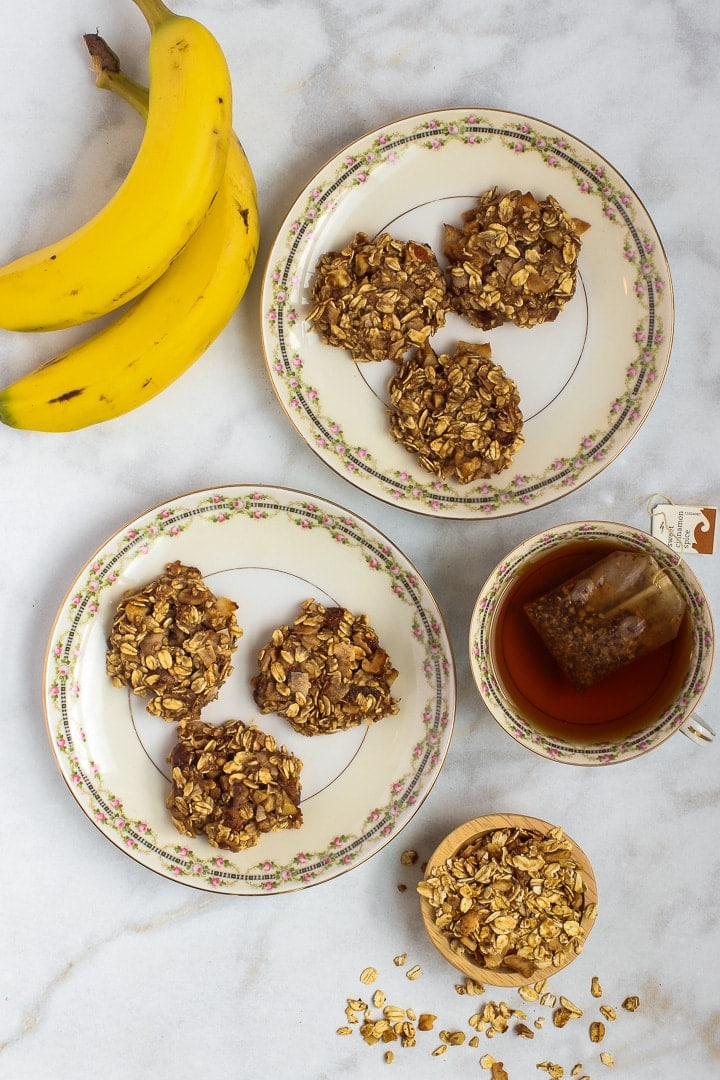 Vegan oatmeal cookies on tow antique china plates; two banana, small bowl of granola and cup of tea on white marble.