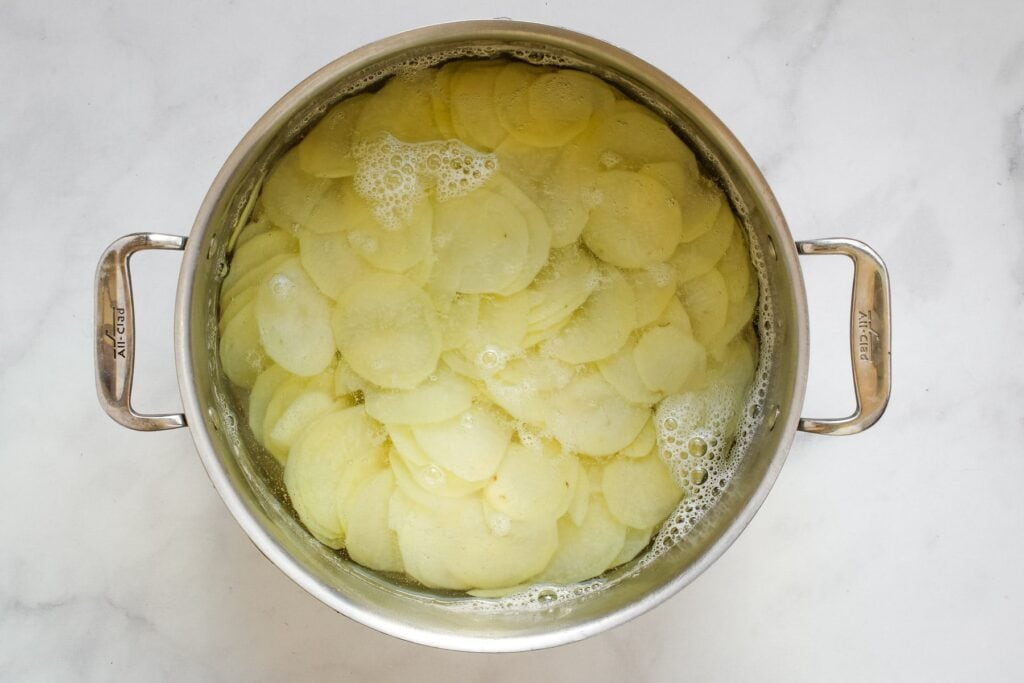 potato slices in a pot of boiling water