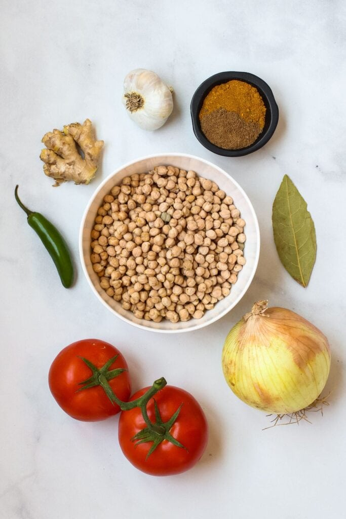 Chana masala ingredients: chickpeas, yellow onion, garlic, ginger, tomato, jalapeño pepper, garam masala, curry powder.