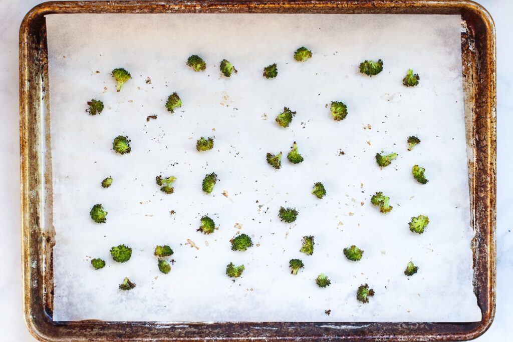 Broccoli florets roasted on a baking sheet with parchment paper.