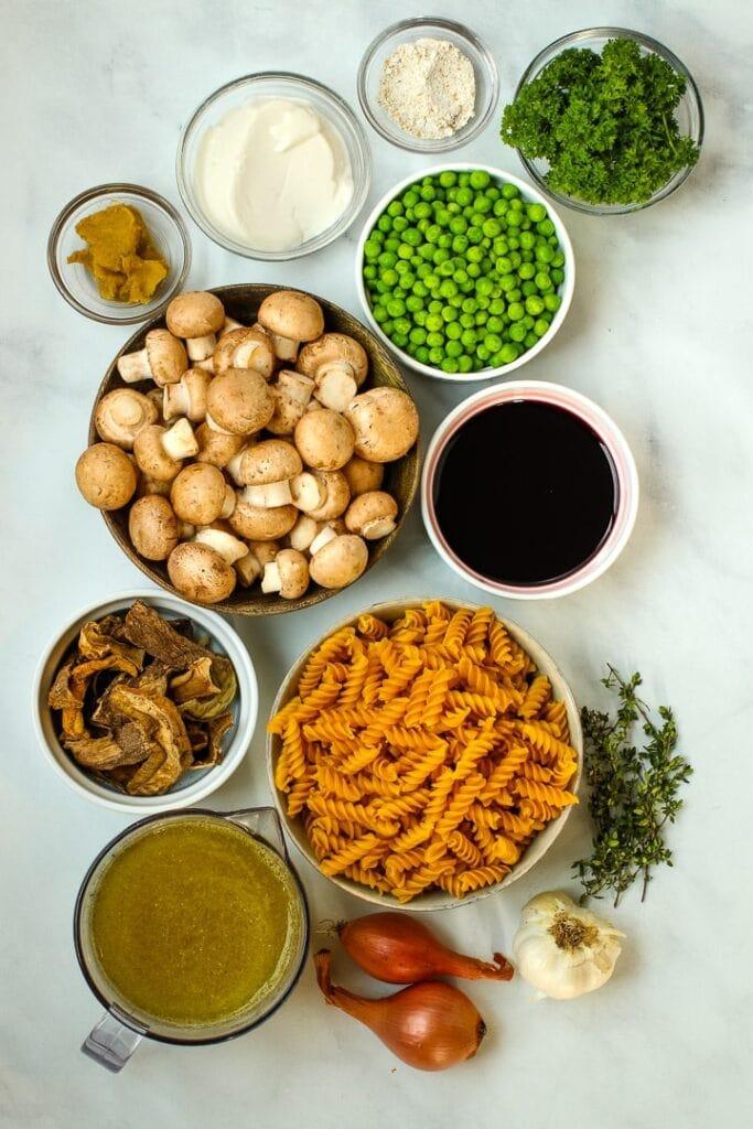 Mushroom stroganoff ingredients: pasta, mushrooms, dried porcini mushrooms, shallots, garlic, thyme, peas, plant-based yogurt, broth, flour and parsley.