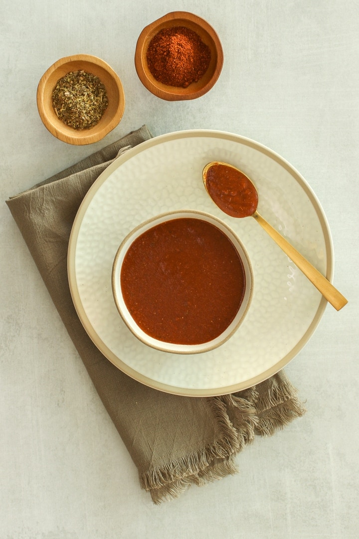 Ivory bowl of enchilada sauce on an ivory plate with spoon, on brown napkin, with dishes of oregano and chili powder.