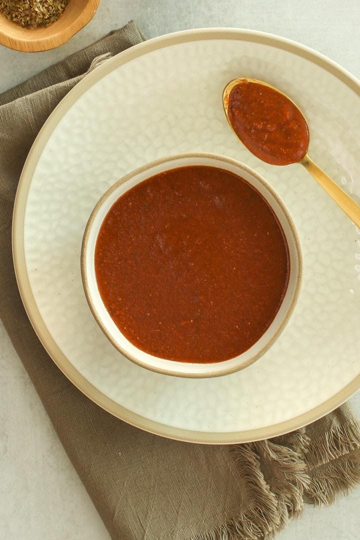 Bowl of vegan enchilada sauce and spoon close up.