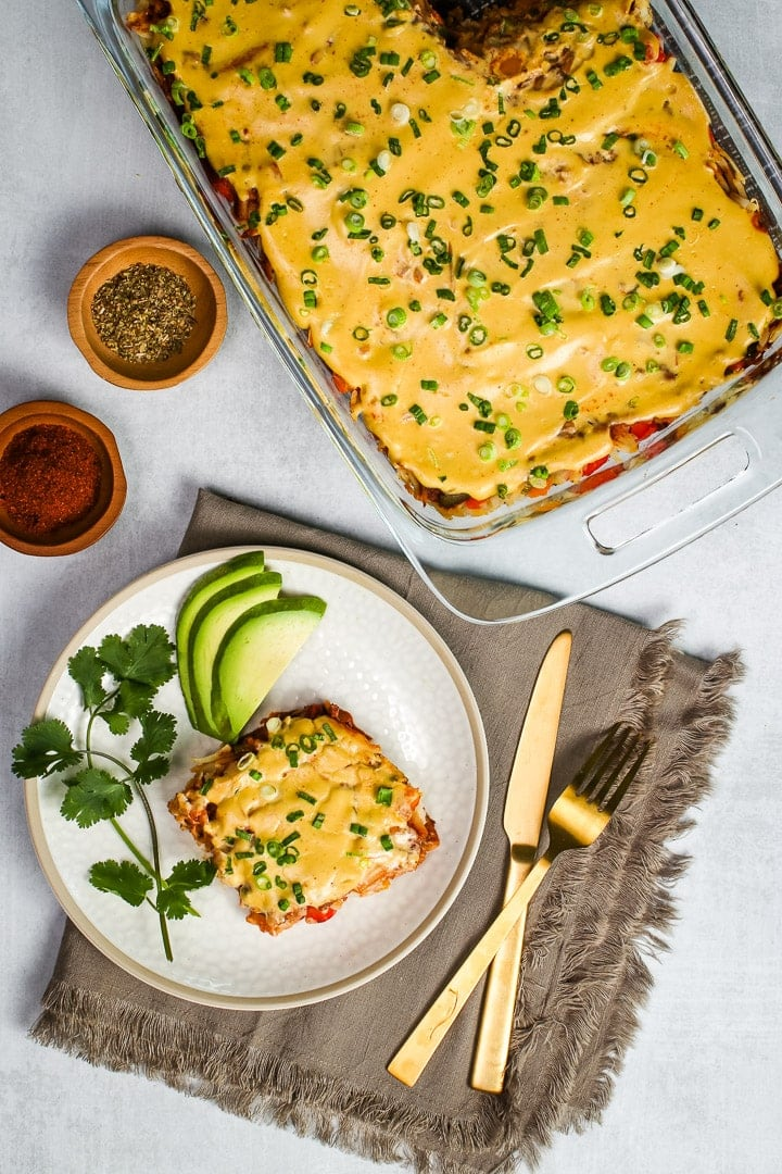 Plate with serving of Mexican breakfast casserole, with avocado and cilantro. Baking dish with casserole in background.