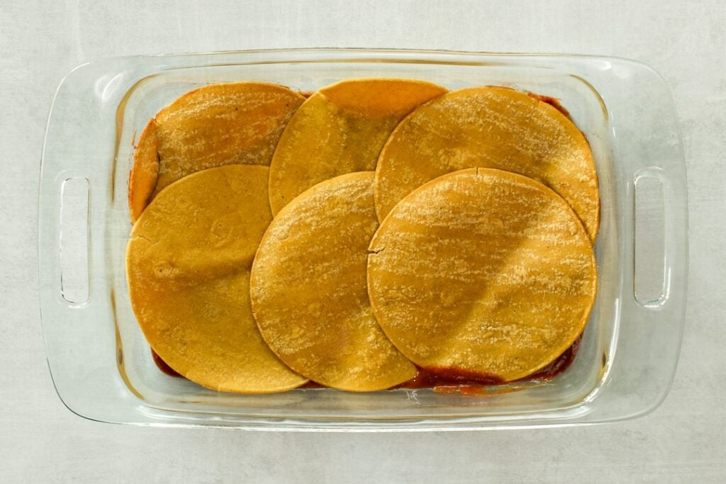 Layer corn tortillas over the enchilada sauce in the baking dish.