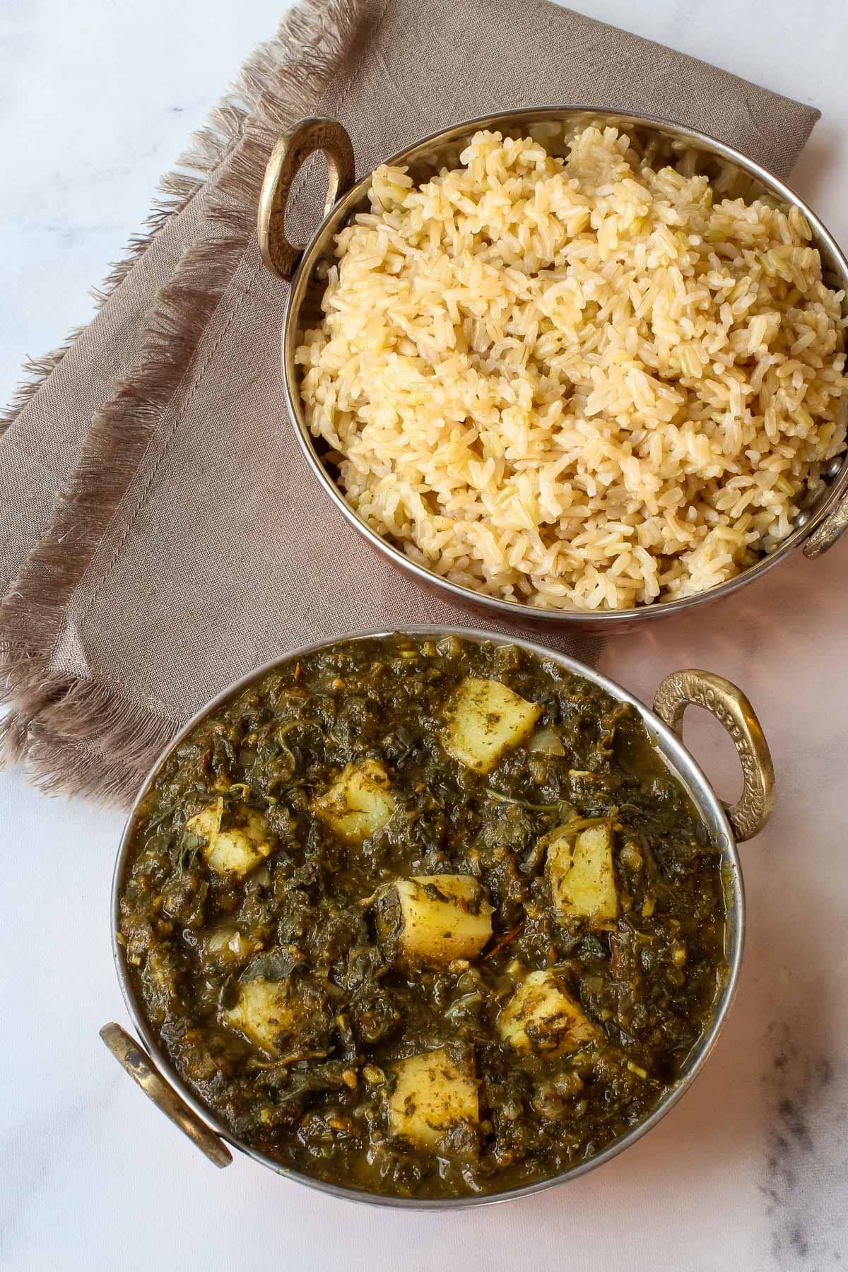Copper dishes of spinach potato curry and brown rice.