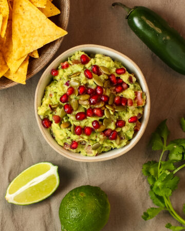 vegan guacamole with chips, pepper and lime on brown towel.